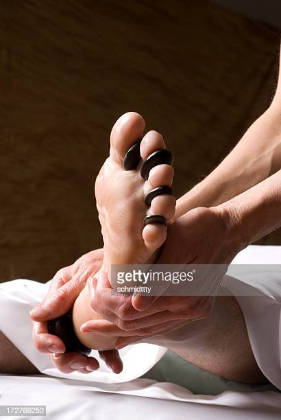 hot stone reflexology foot massage ii - reflexology stock photos and pictures