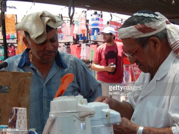 A hot summer day at the market, senior man still working, selling beverages
