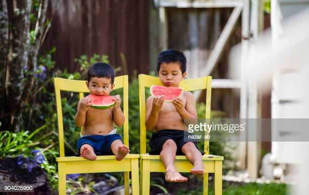 Hot summer kids eating watermelon in backyard.