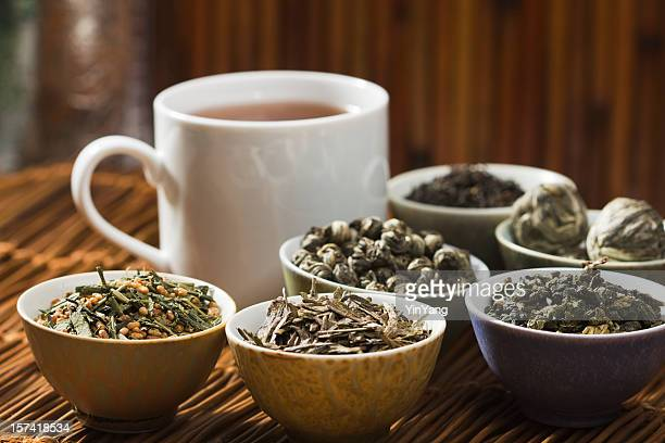 hot tea and leaves, tasting of variety of green and black tea - tea leaves stock photos and pictures