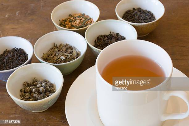 hot tea in cup near leaf varieties for tasting selections - tea leaves stock photos and pictures