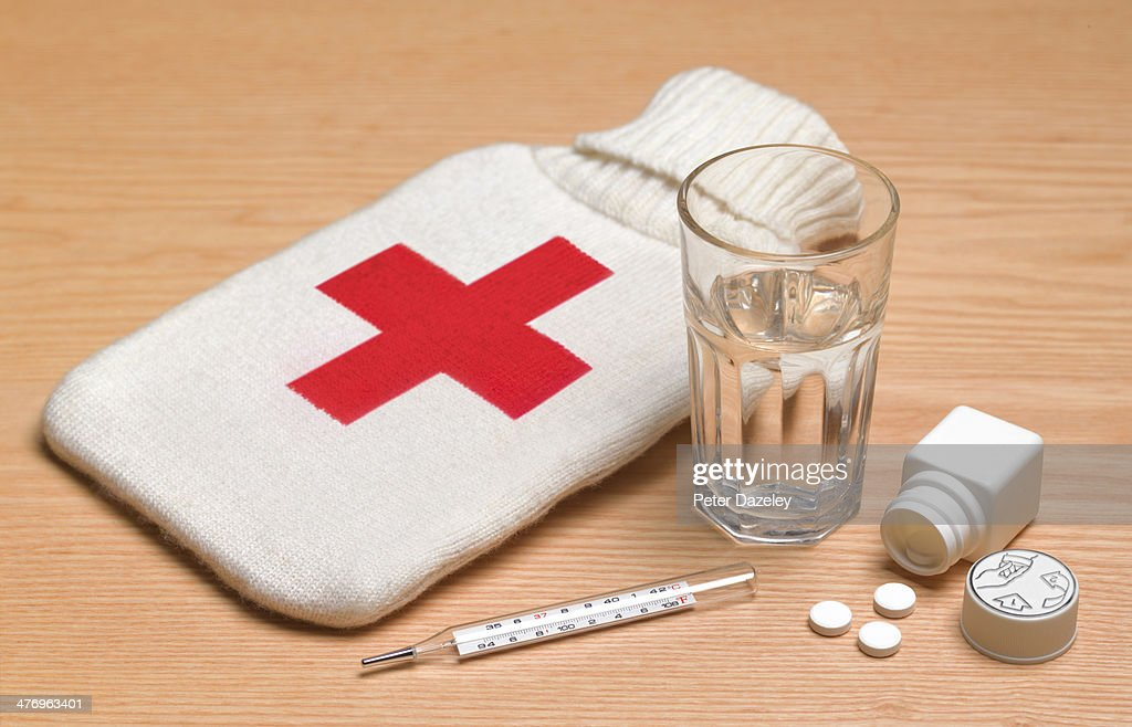 Hot water bottle and pills : Stock Photo