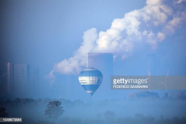 A hotair balloon drives past the steam of the chimneys of the Niederaussen lignitefired power plant above the morning fog in Roggendorf western...