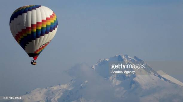 Hotair balloon glides through the sky as snow covered Mount Erciyes is seen from the historical Cappadocia region a UNESCO world heritage site in...