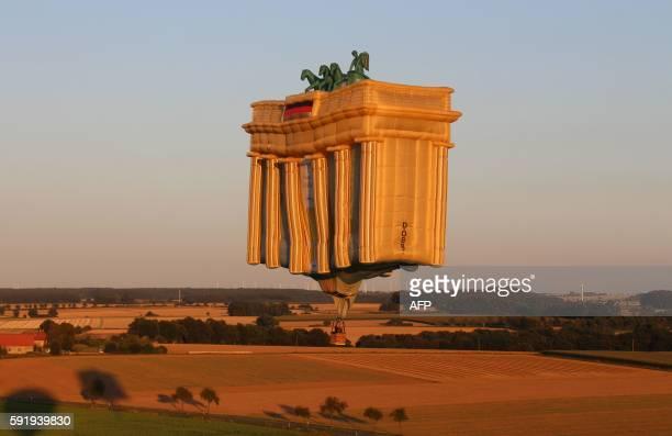 A hotair balloon in the shape of Berlin's Brandenburg Gate flies over fields near Bad Sassendorf western Germany on August 18 2016 It was the last...