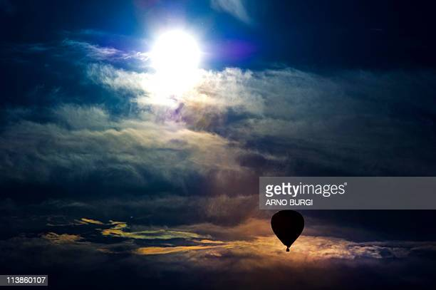 A hotair balloon moves through the sky as the sun shines in the eastern German city of Dresden on May 8 2011 as temperatures rose to a summerly 24...