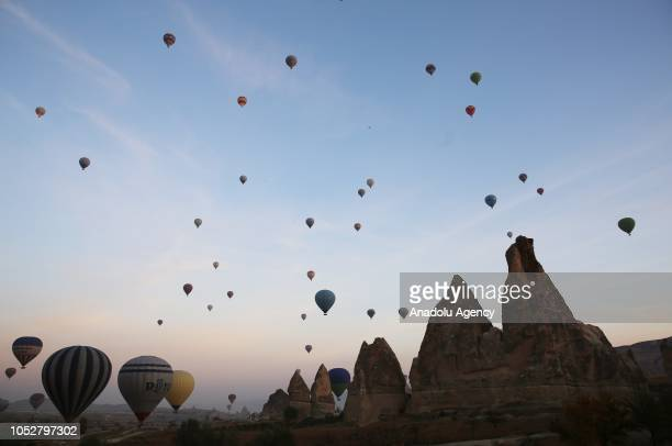 Hotair balloons fly over the picturesque hills of Cappadocia which is in the UNESCO World Heritage List during autumn in Nevsehir Turkey on October...