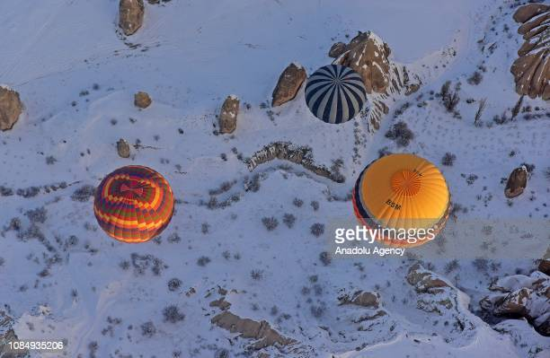 Hot-air balloons glide above fairy chimneys in snow-covered Cappadocia region, located in Central Anatolia's Nevsehir province, Turkey on January 19,...