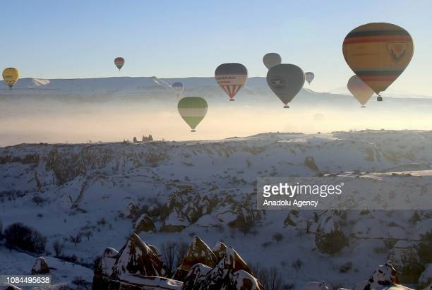 Hot-air balloons glide above snow covered fairy chimneys in the historical Cappadocia region, located in Central Anatolia's Nevsehir province, Turkey...