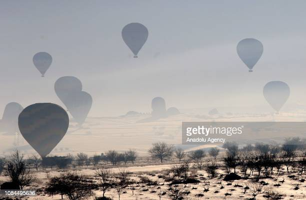 Hot-air balloons glide above the snow covered Cappadocia region, a UNESCO world heritage site, located in Central Anatolia's Nevsehir province,...