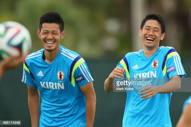 Hotaru Yamaguchi and Shinji Kagawa laugh during a Japan training session at North Greenwood Recreation & Aquatic Complex on June 1, 2014 in...