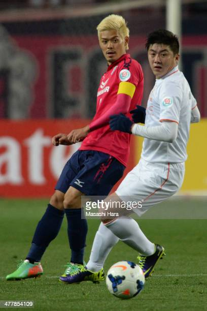 Hotaru Yamaguchi of Cerezo Osaka and Cui Peng of Shandong Luneng FC compete for the ball during the AFC Champions League Group E match between Cerezo...