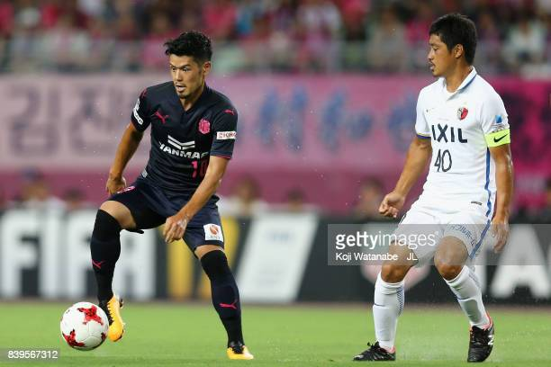 Hotaru Yamaguchi of Cerezo Osaka controls the ball under pressure of Mitsuo Ogasawara of Kashima Antlers during the JLeague J1 match between Cerezo...