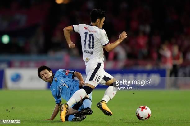 Hotaru Yamaguchi of Cerezo Osaka is tackled by Shintaro Kurumaya of Kawasaki Frontale during the JLeague J1 match between Kawasaki Frontale and...