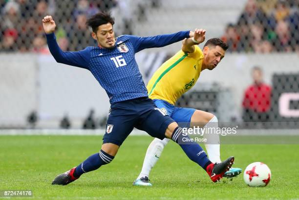 Hotaru Yamaguchi of Japan and Giuliano of Brazil battle for possession during the international friendly match between Brazil and Japan at Stade...