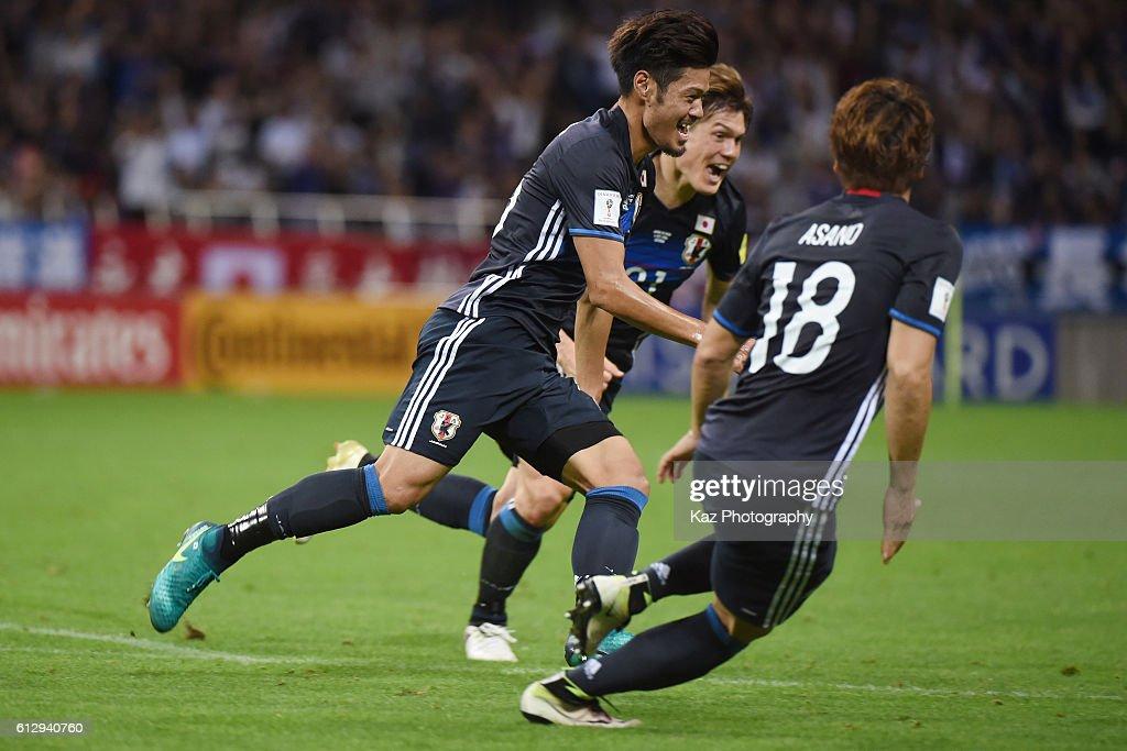 Hotaru Yamaguchi of Japan celebrates the winner with his team mates, Gotoku Sakai and Takuma Asano of Japan during the 2018 FIFA World Cup Qualifiers match between Japan and Iraq at Saitama Stadium on October 6, 2016 in Saitama, Japan.