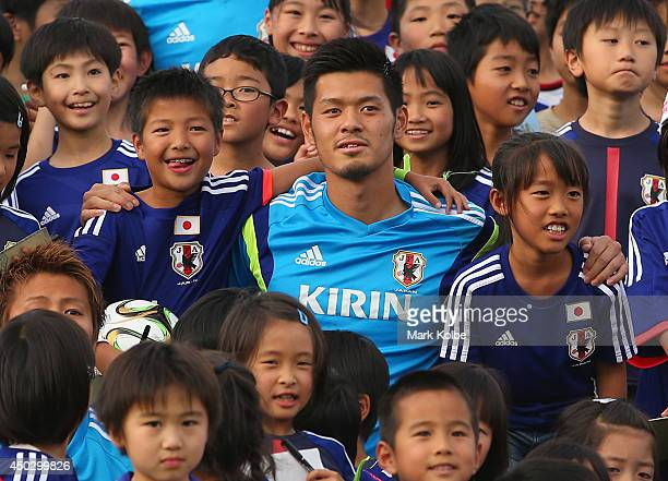 Hotaru Yamaguchi of Japan poses with children as the team pose for a group photo with children from the local community during a Japan training...