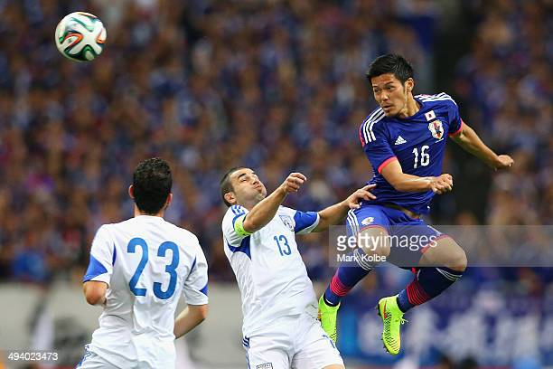 Hotaru Yamaguchi of Japan wins the ball over Konstantinos Makridis of Cyprus during the Kirin Challenge Cup international friendly match between...