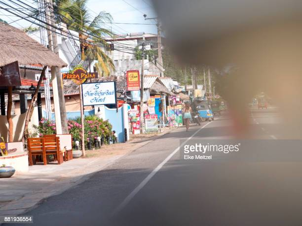 Hotel and restaurant lined street in Arugam Bay shot from the back of a motor bike