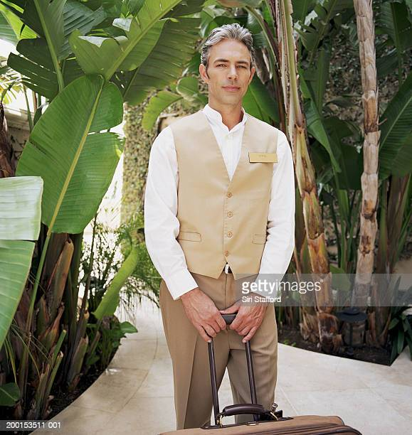 hotel attendant holding luggage, portrait - doorman stock photos and pictures