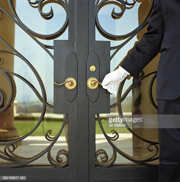Hotel attendant opening door (mid section)