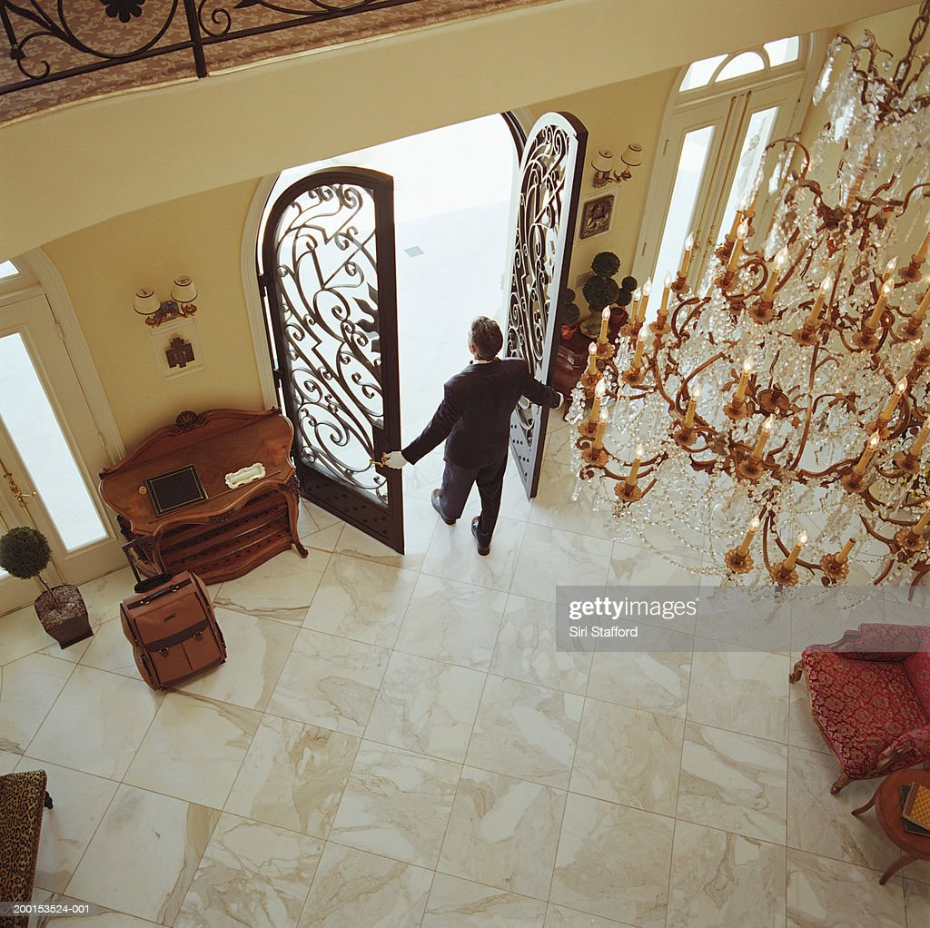 Hotel attendant opening doors, elevated view : Stock Photo