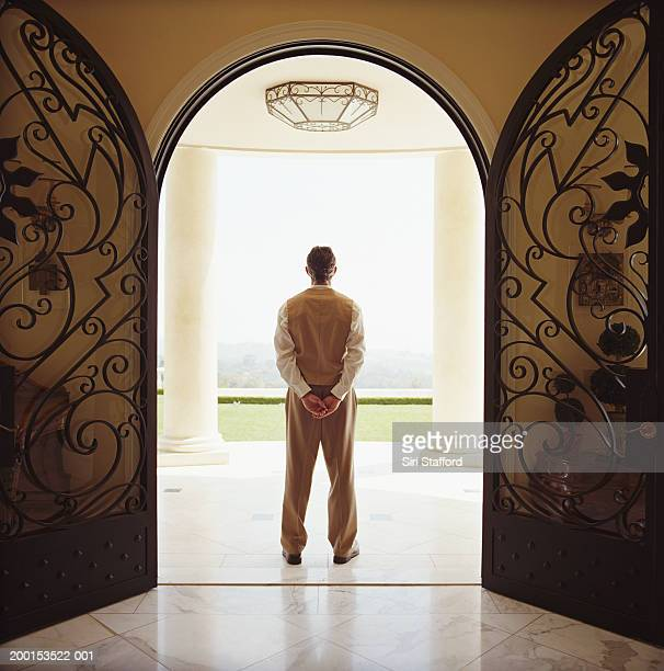 Hotel attendant standing by doorway, rear view