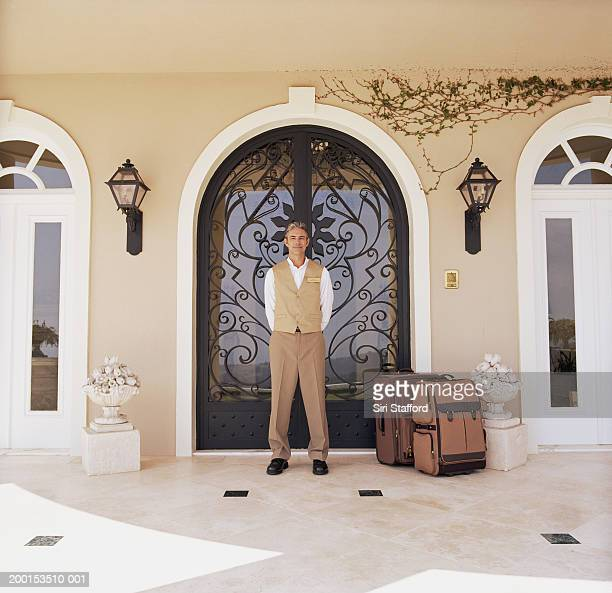 hotel attendant standing by doorway with luggage, portrait - doorman stock photos and pictures