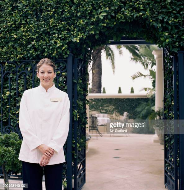 Hotel attendant standing by gate, portrait