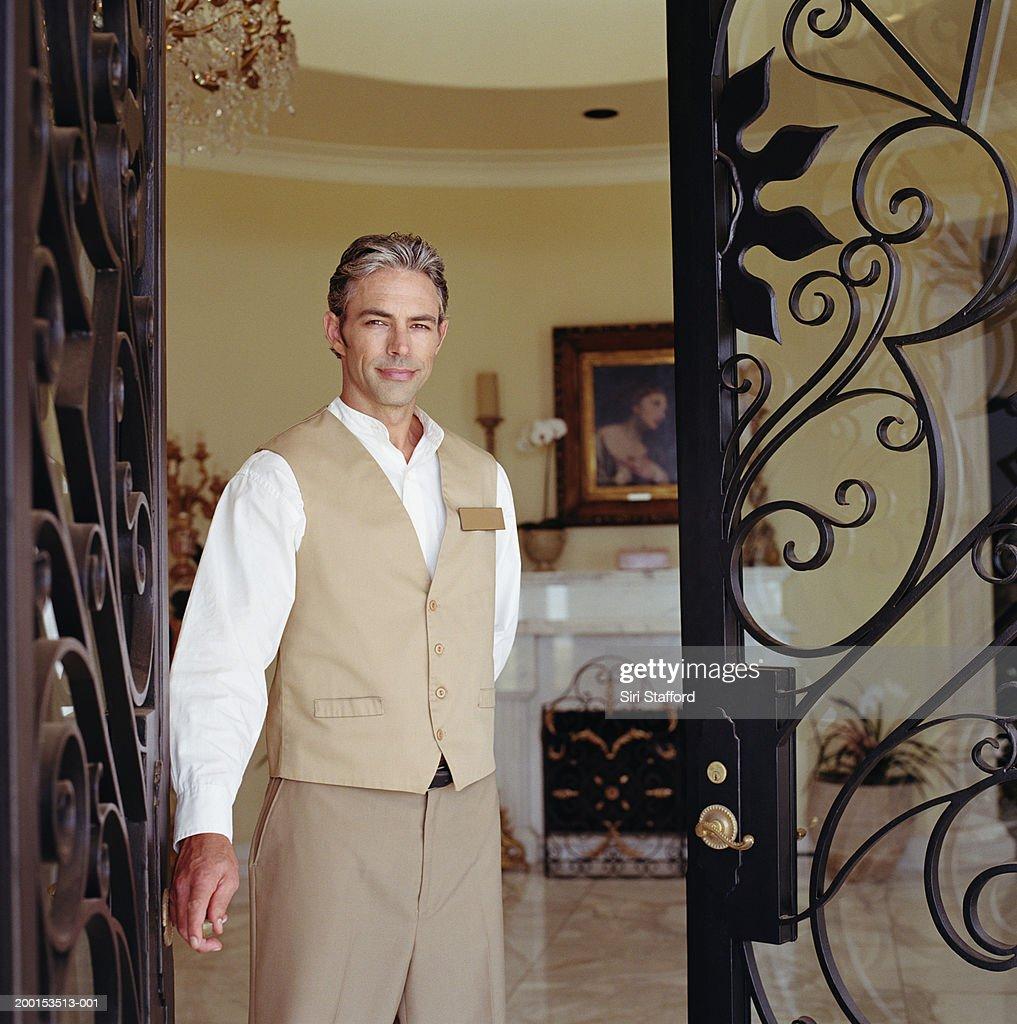 Hotel attendant standing in doorway, portrait : Stock Photo