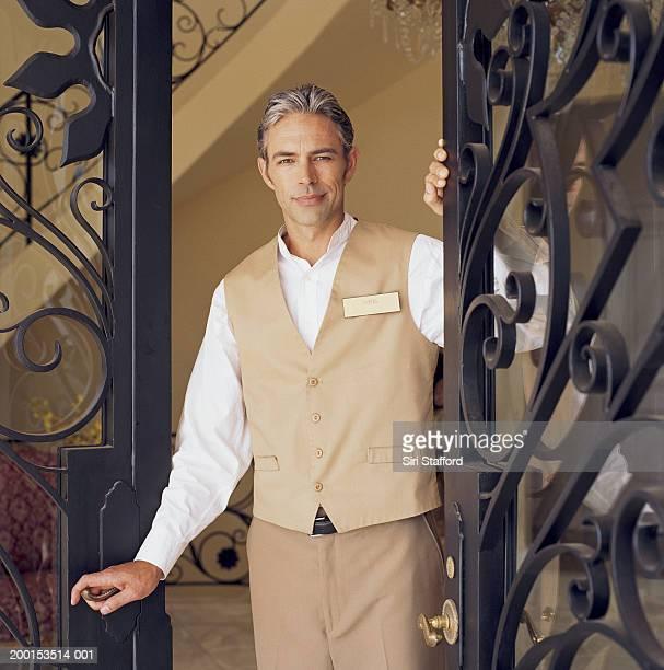hotel attendant standing in doorway, portrait - doorman stock photos and pictures