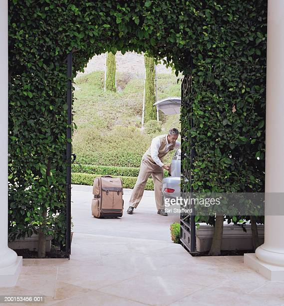 Hotel attendant unloading luggage from car