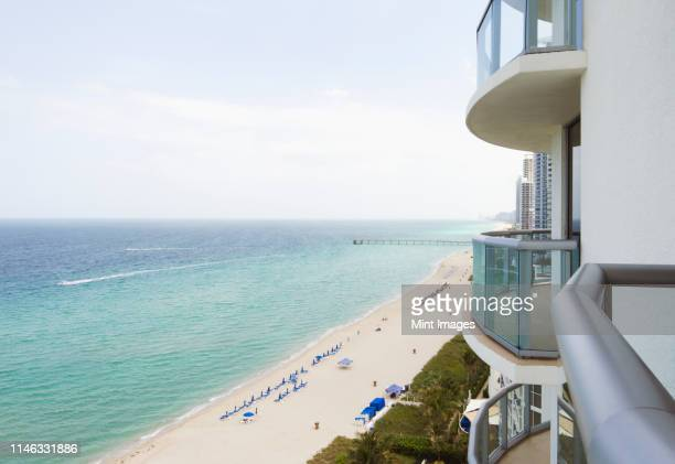 hotel balcony overlooking urban beach - southeast stock pictures, royalty-free photos & images