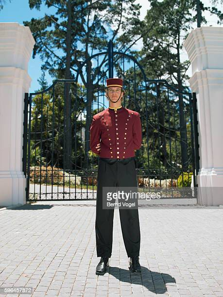 Hotel bellhop in front of gates