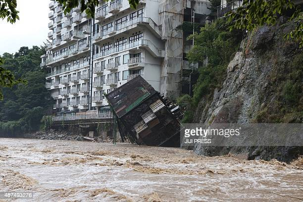 A hotel building falls into the floodwaters at Nikko mountain resort in Tochigi prefecture north of Tokyo on September 10 2015 Authorities in central...