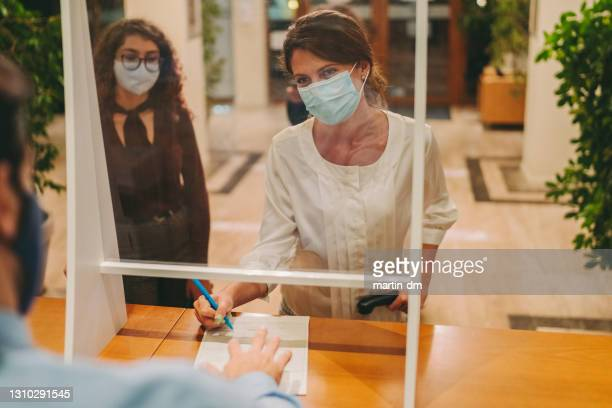 hotel check in during covid-19 pandemic - guest stock pictures, royalty-free photos & images