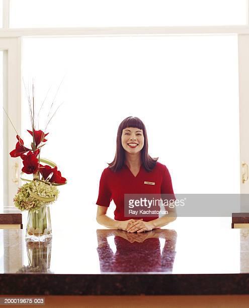 Hotel clerk at front desk, smiling
