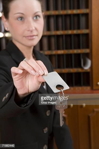 Hotel clerk handing over key to hotel room