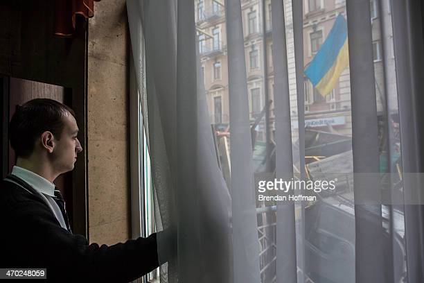 A hotel clerk looks out the lobby window at a barricade that was constructed on an adjacent street overnight near the perimeter of Independence...