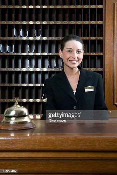Hotel clerk standing behind desk at hotel reception