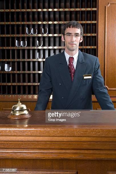 Debout derrière l'employé de bureau à la réception de l'hôtel