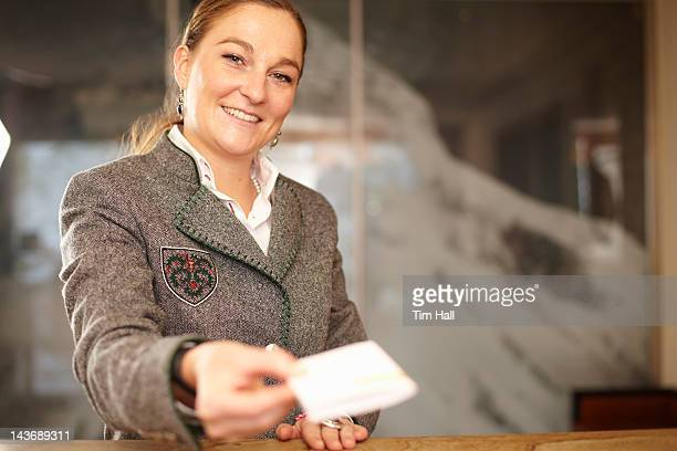 Hotel concierge with card at desk