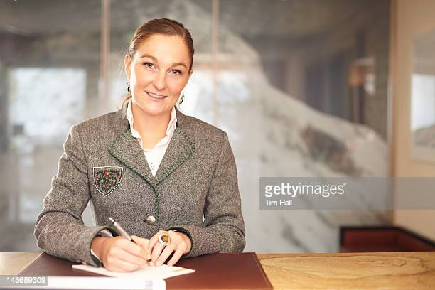hotel concierge writing at desk - vorarlberg stock photos and pictures