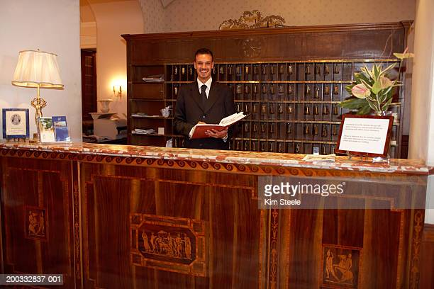 Hotel desk clerk holding guest book, standing behind counter, portrait