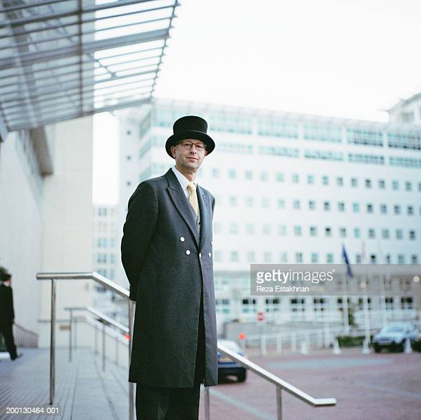 hotel doorman in front of entrance (grainy) - overcoat stock pictures, royalty-free photos & images