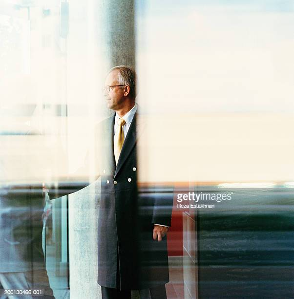 hotel doorman standing by revolving door - doorman stock photos and pictures