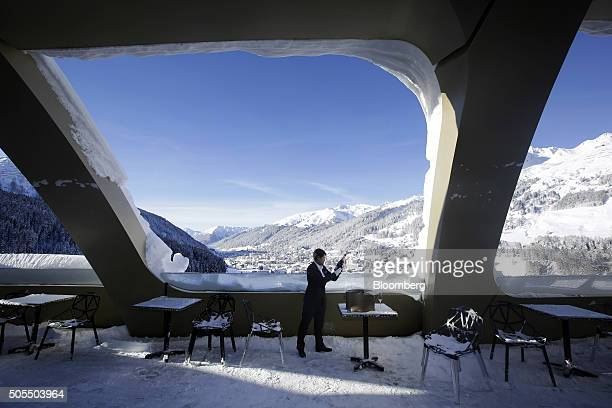 A hotel employee checks a bottle of champagne as he stands on the snow covered bar terrace of the InterContinental Hotel Davos operated by...