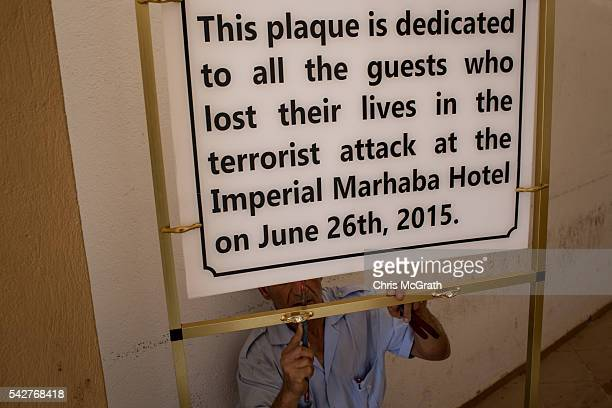 A hotel employee fixes a memoriam sign in preparation for the anniversary of the Sousse Beach attack at the closed Imperial Marhaba Hotel on June 24...
