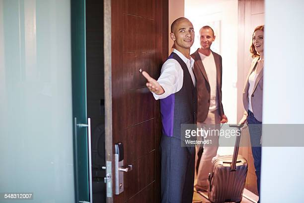 Hotel employee showing hotel guests their room