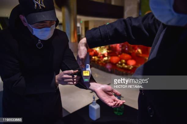 A hotel employee takes the temperature of a person that just arrived at the premise in Wuhan on January 24 2020 The death toll in China's viral...